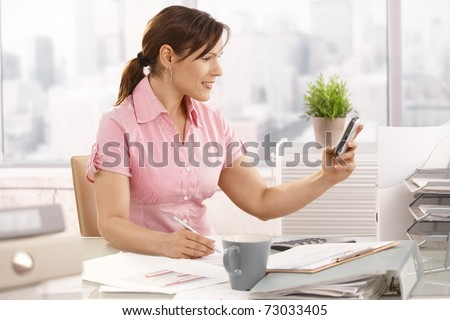 Casual office worker sitting at office using mobile phone, smiling.?