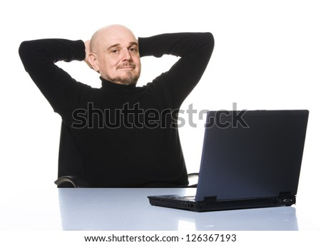 Casual older man smiling with hands behind his head. A laptop computer in front of him on a table. Isolated on white background.