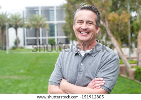 casual portrait of a mature, happy man taken outside