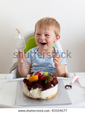 Casual portrait of a two-yer-old eating a cake