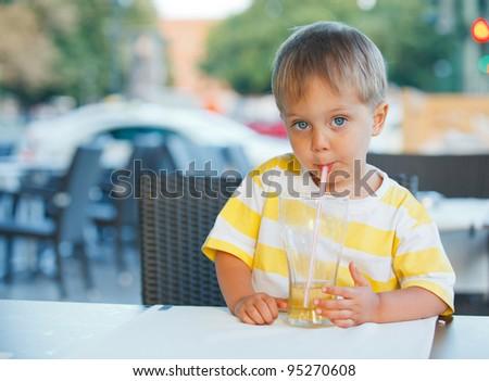 Casual portrait of adorable little boy drinking juice in outdoor restaurant