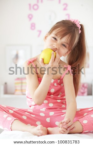Casual portrait of cute child eating apple in bed