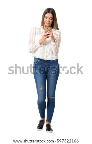 d67f7eb77e2 Casual pretty young woman typing on the smart phone. Full body length  portrait isolated over
