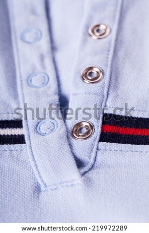 Casual shirt collar and texture detail with a colorful red and blue stripe and metal studs to close the open neck collar