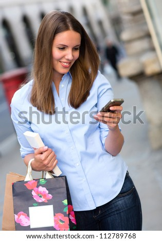 Casual shopping woman sending a text message from her phone