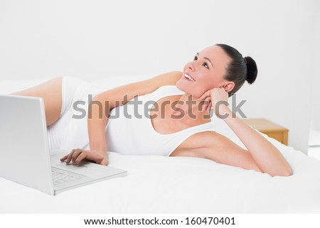 Casual smiling young woman looking up while using laptop in bed