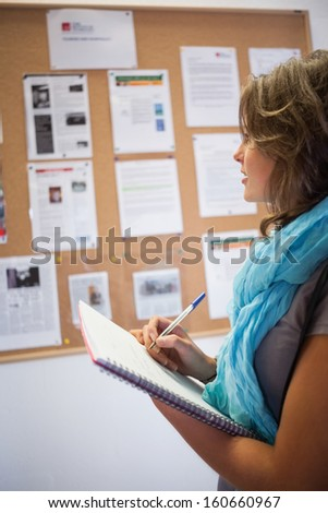 Casual student taking notes in front of notice board in school