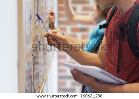 Casual students searching something on notice board in college