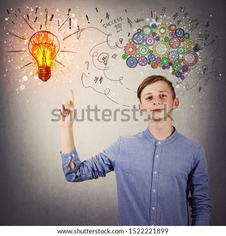 Casual teen boy pointing his index finger up showing a bright light bulb on the wall. Idea concept, positive thinking as colorful gear brain above head, create a genius. Mental development symbol.