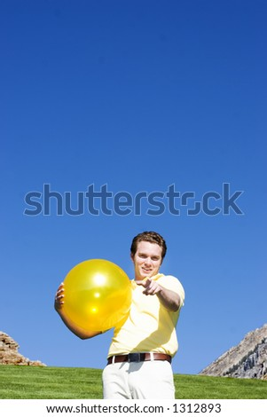 Casual white man points finger at the screen with a small smile on his face with a yellow ball in his hands under a blue sky - stock photo