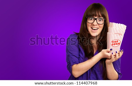 Casual Woman Holding Popcorn Container Isolated On Purple Background
