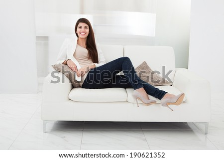 Casual woman in jeans sitting on a couch in her living room #190621352