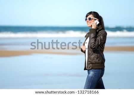 Casual woman talking on cellphone and walking on the beach on spring sunny day. Beautiful happy caucasian brunette model.