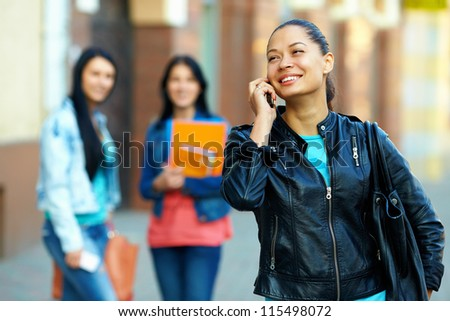 casual woman talking on the mobile phone, while walking the street