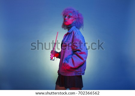 casual woman with trendy clothes drinking a retro beverage on neon lights