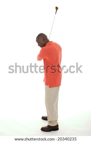 Casual young African American man in a bright orange golf shirt swinging a golf club. - stock photo