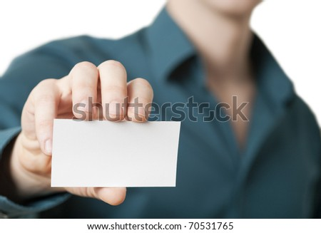 Casual young businessman holding business card. Close up shot focused on the hand holding the card with intentionally shallow depth of field.
