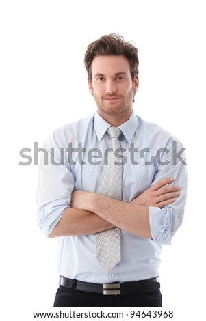 Casual young businessman standing arms crossed, smiling.?
