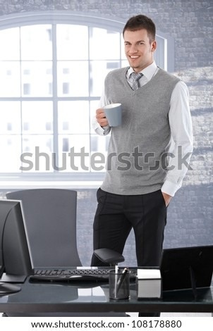 Casual young businessman standing in bright office, drinking tea, smiling.
