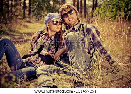 Casual young couple sitting together on a grass on a sunny day.