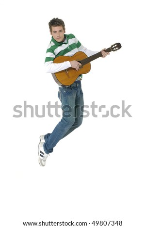 casual young man jumping with guitar on white