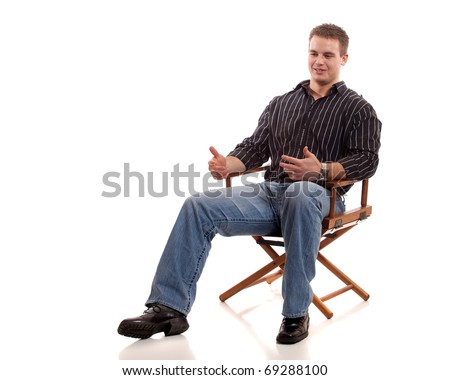 Casual young man seated in directors chair.