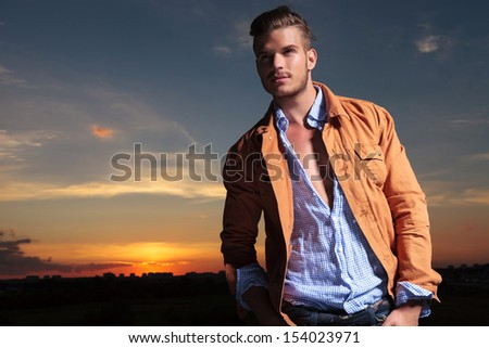 casual young man standing outdoor and looking up while holding both hands in his pockets with the sunset behind him