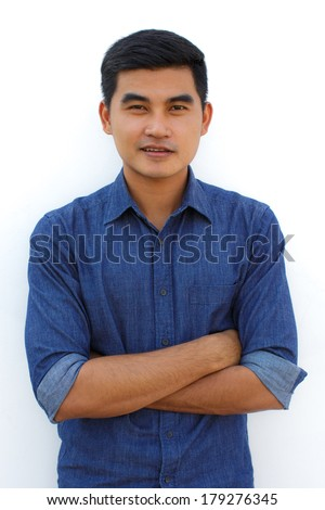 casual young man standing with his arm crossed over white background