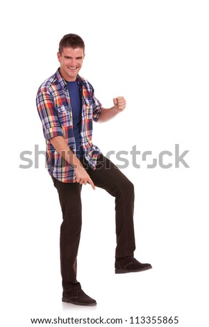 Casual young man stepping on something, pointing at it and smiling. Young man posing like Goliath, showing his superiority