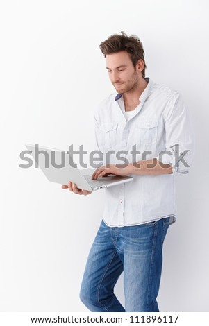 Casual young man using laptop, standing by wall.