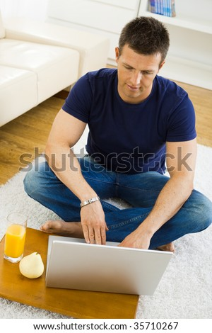 Casual young man working at home on his laptop computer, sitting on floor, looking at screen. High angle view.