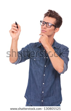 casual young man writing something on an imaginary screen and looking pensively at it. isolated on a white background