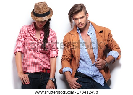 casual young woman looking down while her boyfriend looks to the camera and poses