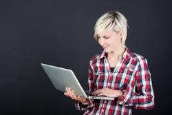 Casual young woman with laptop against black background