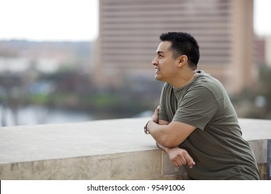Stock photo of a casually dressed Hispanic man looking out from a stone balcony.
