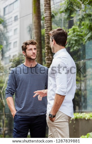 Casually dressed men talking in city