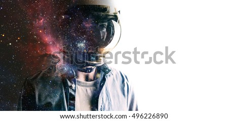 Casually dressed sad looking man in a large helmet with bright stars and galaxies projected on the shield and behind his back with white background in front of him. Double exposure