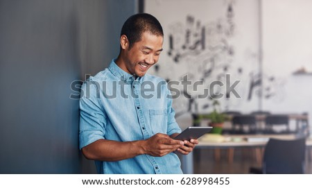 Casually dressed young Asian designer smiling and using a digital tablet while leaning against a gray wall in a modern office