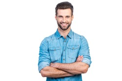Casually handsome. Confident young handsome man in jeans shirt keeping arms crossed and smiling while standing against white background