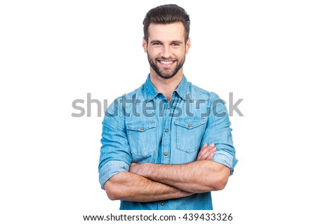Casually handsome. Confident young handsome man in jeans shirt keeping arms crossed and smiling while standing against white background  - Shutterstock ID 439433326