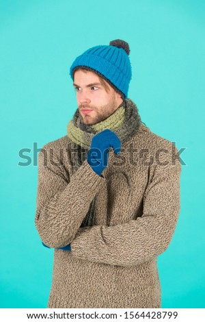 Casually handsome. Man handsome unshaven guy wear winter accessories on blue background. Shopping concept. Emotional expression. Winter season sale. Hipster knitted winter hat scarf and gloves.
