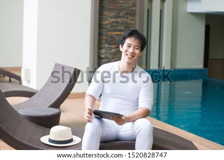 Casually white dressed young Asian traveler smiling and using a digital tablet while leaning against a gray wall in a modern swimming pool, freedom lifestyle.