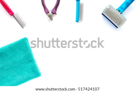 Cat and dog grooming tools: fine toothed comb, wide toothed comb, slicker brush, small nail clipper and a microfiber towel isolated on white background.