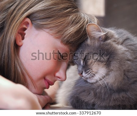 Cat and girl nose to nose. Tenderness, love, friendship. Sweet and loving picture of friendship and child cat