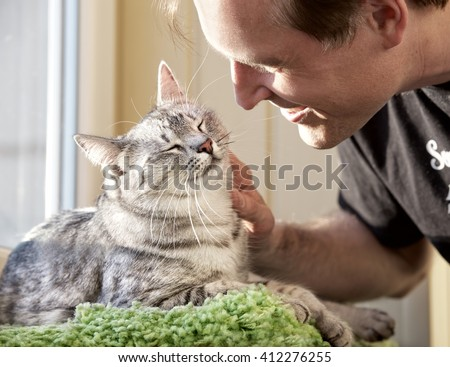 Cat and man, portrait of happy cat with close eyes and young man , man playing with the cat. Handsome Young Animal-Lover Man, Hugging and Cuddling his Gray Domestic Cat Pet