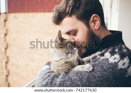 Cat and man, portrait of happy cat with close eyes and young man, people playing with the kitten. Handsome Young Animal-Lover Man, Hugging and Cuddling his Gray Domestic Cat Pet #742177630