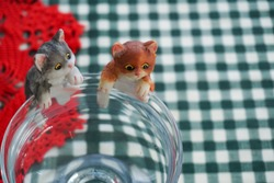 Cat dolls looking for fish in a glass of water.