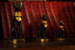 Cat figurines sitting on a shelf in front of dusty vintage bookshelf Egyptian cat figurines