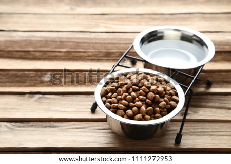 Cat food and water in bowls on wooden table