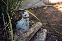 Cat Garden Figurine in Blue Shirt With Pink Roses in Flower Bed on Sunny Day - Horizontal